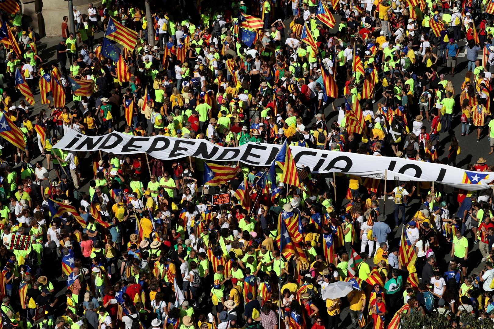 """A man carries a sign that reads """"Spain for sale"""" next to a huge banner reading """"Independence Now"""" during a rally on Catalonias national day La Diada in Barcelona"""
