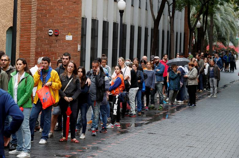 Voters wait in queue outside a polling station during the banned independence referendum in Barcelona
