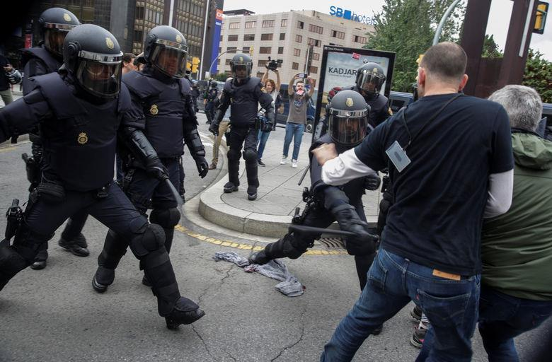 Spanish police scuffle with people outside a polling station for the banned independence referendum in Tarragona