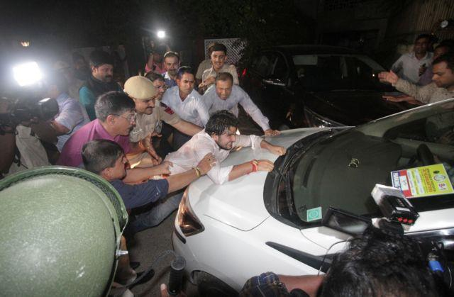 Supporter of Indias former Finance Minister Chidambaram tries to stop a vehicle carrying Chidambaram after he was arrested by CBI officials in New Delhi